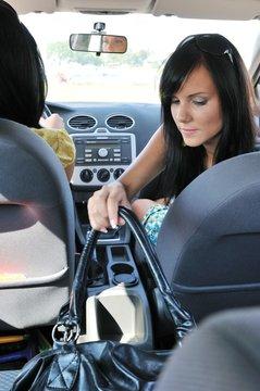 Young woman in car reaching handbag