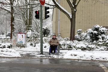 junger Rollstuhlfahrer an einer roten Ampel wartend