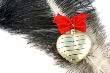 Golden heart with red bow on ostrich feather