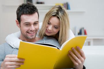 Young couple reading magazine