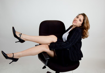 Happy businesswoman playing in a chair
