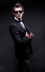 elegant young man wearing suit, bow tie and sunglasses