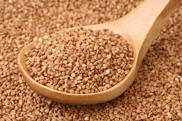Small buckwheat groats in a wooden spoon