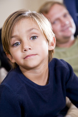 Cute five year old boy with father in background