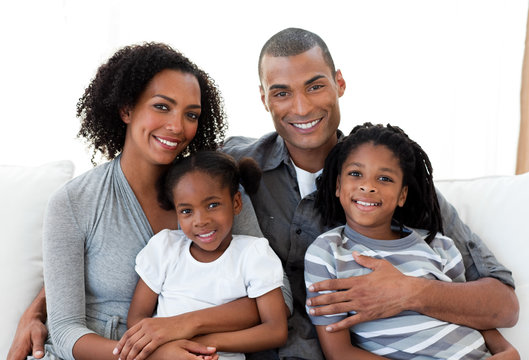Loving african american family sitting on the sofa together