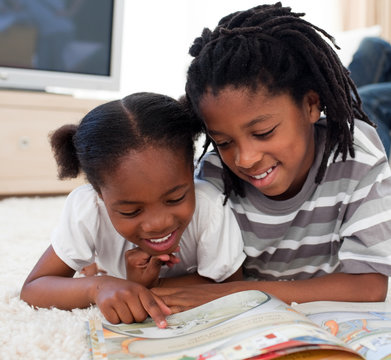 Concentrated siblings reading a book
