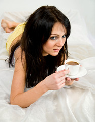 Woman in bed drinking a coffe