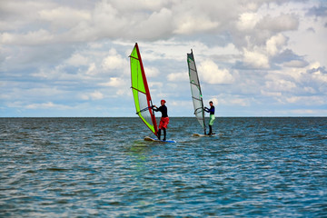 Windsurfers on a highlighted sea with blue sky and wispy clouds