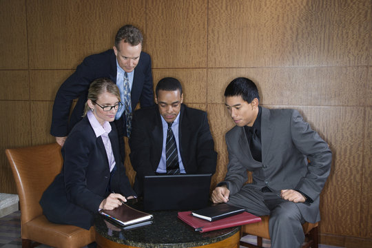 Businesspeople Gathered Around a Laptop