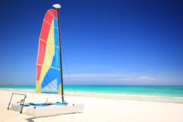 A colorful catamaran sailboat on a gorgeous tropical beach