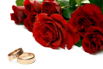 Red roses and wedding rings isolated on white