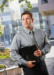 Businessman with briefcase outside office