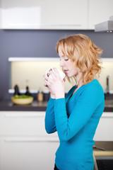 junge frau trinkt eine heiße tasse tee in der küche