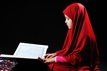 Muslim girl on black background reading Koran