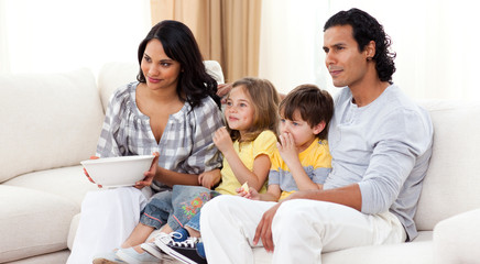 Smiling family watching TV on sofa