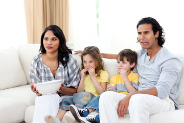 Concentrated family watching TV on sofa