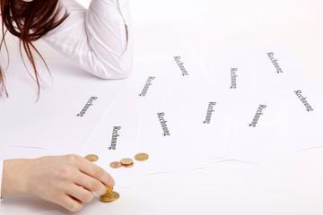 Frau mit Rechnungen und Münzen