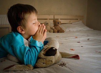 Little boy praying at bedtime