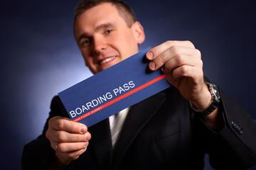Business man holding a boarding pass