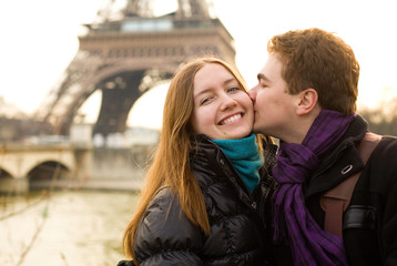 Happy loving couple in Paris, kissing by the Eiffel Tower