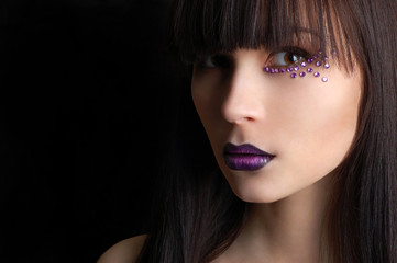 Beautiful woman with violet make-up isolated on black