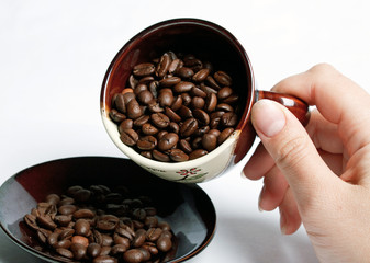 Cup with coffee beans turned by a hand.