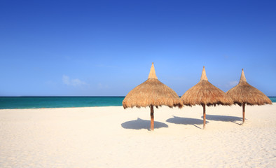 Grass umbrellas on a white sand beach