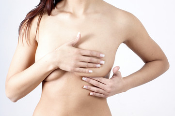 woman checking breats for signs of breast cancer