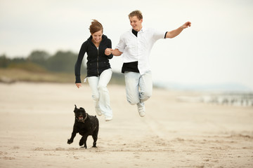 two young people running on the beach jumping