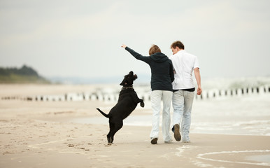 two young poeple runnig on the beach holding tight with dog