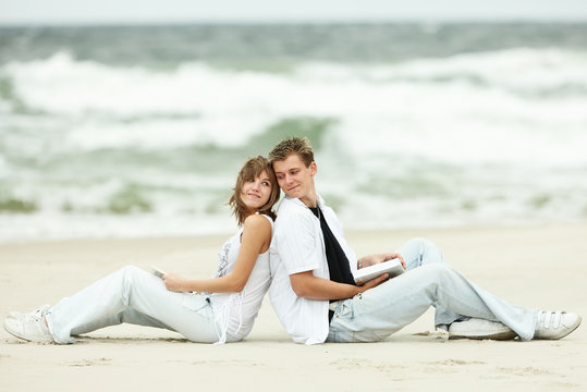 two young couple sitting on the beach