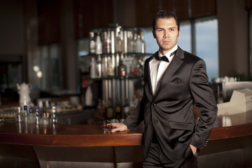 Handsome man in tuxedo at bar holding whisky in hand