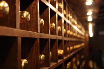 Racks with bottles in a dark wine cellar