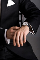 hands of the man in a black suit and expensive watch