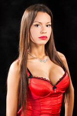 Woman in red corset on dark background