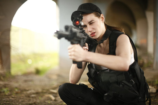 young and attractive woman holding an assault rifle