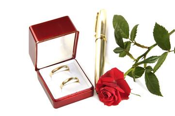 Wedding rings, small red rose and pen on white.