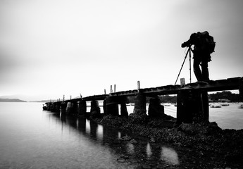 a wooden pier with a man , black and white