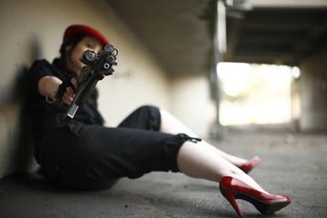 sexy young woman pointing an automatic gun