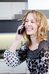 junge frau telefoniert in der küche