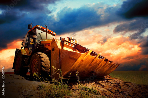 Wall mural Yellow tractor on golden surise sky