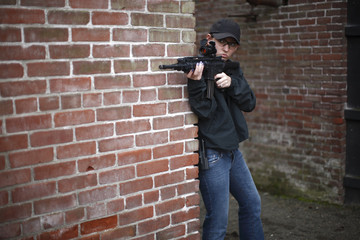 Female police officer aiming rifle.