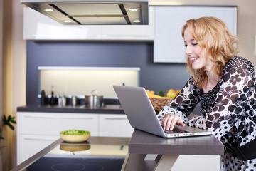 junge frau arbeitet mit dem laptop in der küche