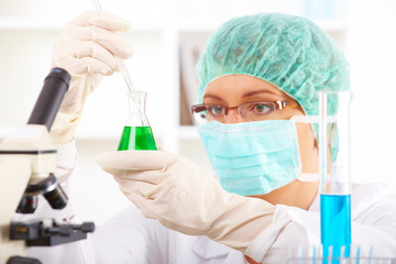 Female researcher holding up a test tube and a retort