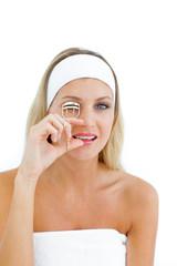 Attractive woman using an eyelash curler