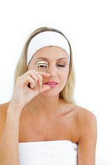 Young woman using an eyelash curler