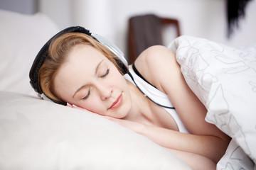 junge frau liegt im bett und hört musik