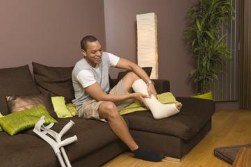 Homme souriant regardant sa jambe plâtrée