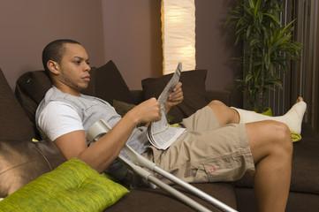 Homme plâtré lisant un journal dans son salon
