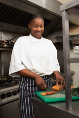 Female Chef Preparing Vegetables In Restaurant Kitchen